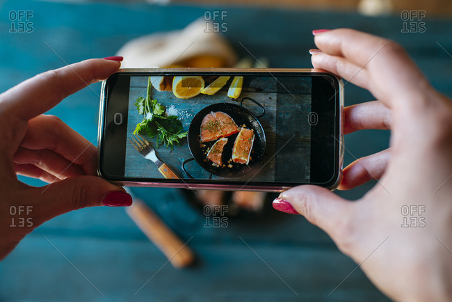 Closeup of hands taking a picture of salmon fillets with parsley and lemon