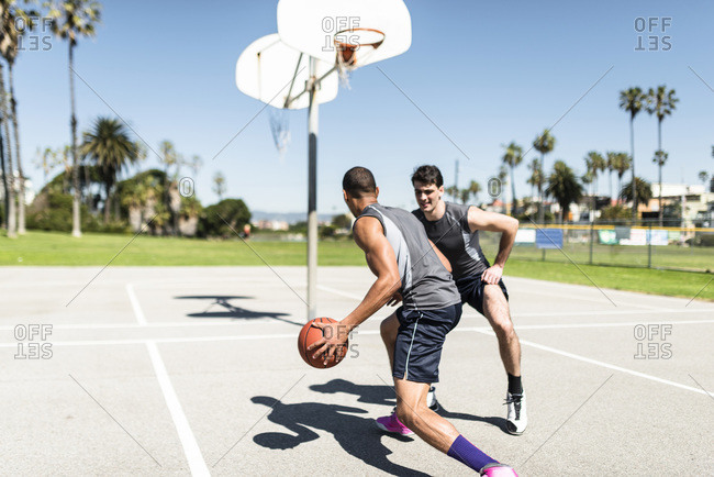 Two young men playing basketball on an outdoor court