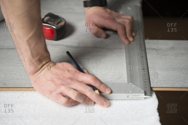 Man measuring with a angle measure, laminate floor