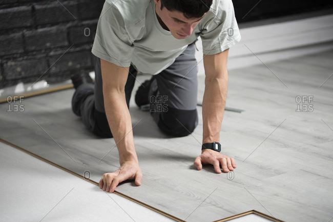 Young man placing a laminate floor