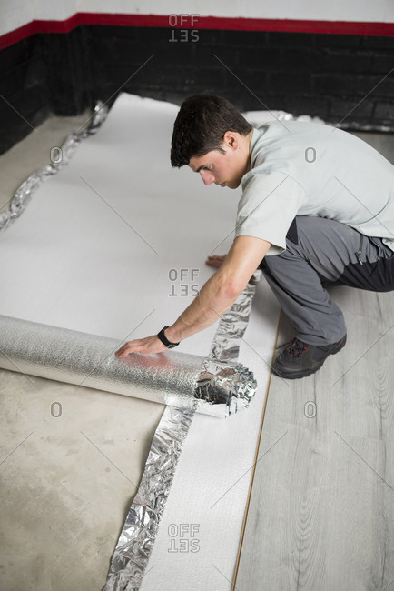 Young man placing a insulating material for a laminate flooring