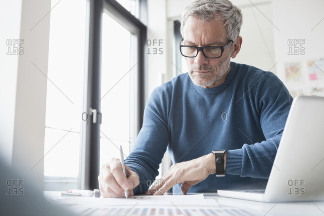 Mature man sitting in office working with laptop and smart watch