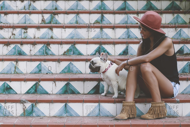 Woman sitting with her dog on stairs