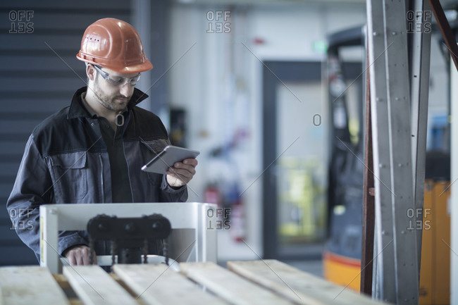 Young technician working with tablet pc, palettes