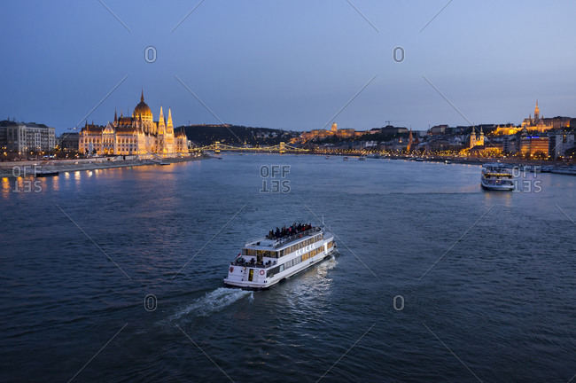 Hungary, Budapest, tourist boats on river danube, parliament building in the background