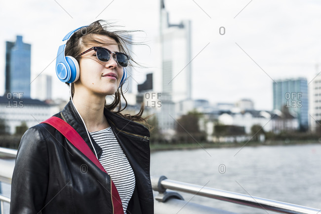 Young woman walking in the city wearing headphones