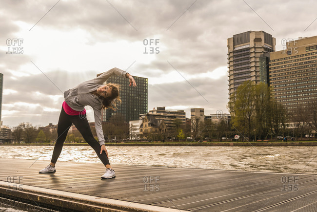 Young woman stretching at the riverseide