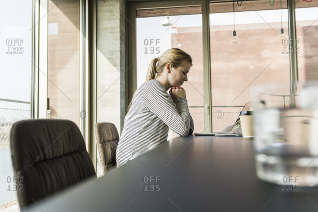 Young woman at desk in office with closed eyes
