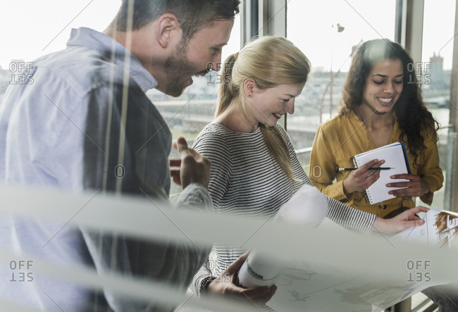 Three smiling colleagues looking at plan in office