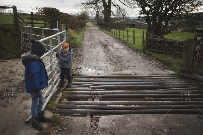 Brothers crossing over a culvert on a country dirt road