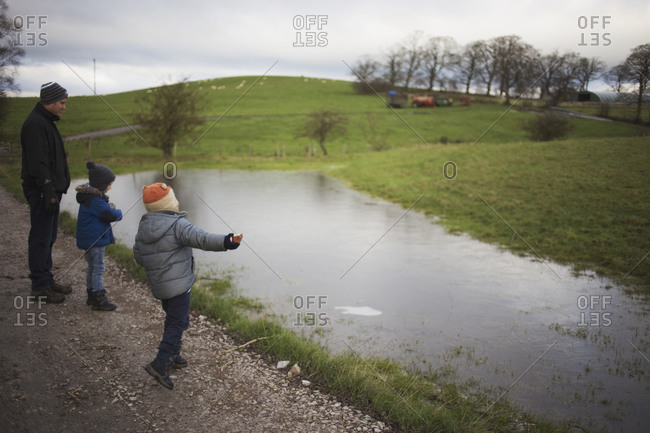 Father and two sons looking at a large puddle in a farm field