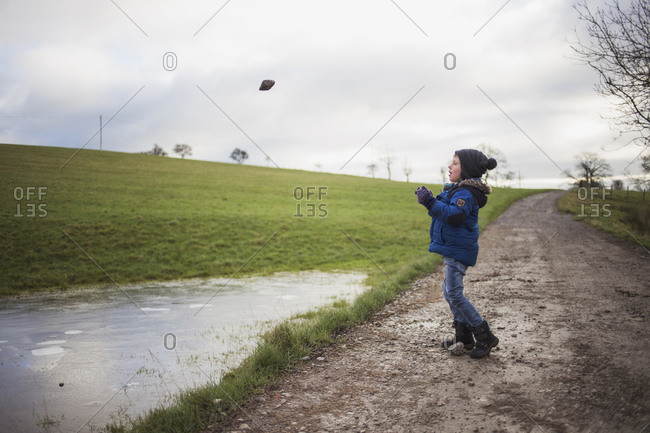 Little boy throwing rocks into a large puddle on a farm