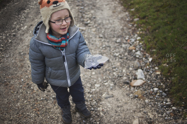 Boy standing on a gravel path holding a thin piece of ice