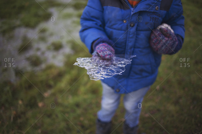 Boy holding a thin piece of ice found in a puddle