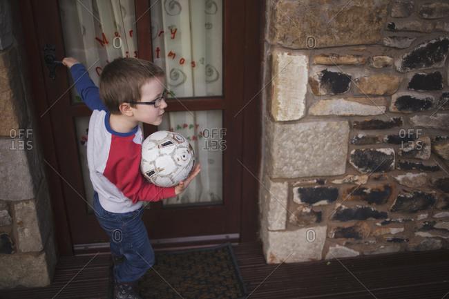 Little boy closing a door while holding a soccer ball