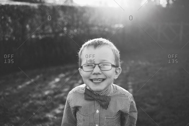 Little boy with glasses in a checkered shirt and bowtie