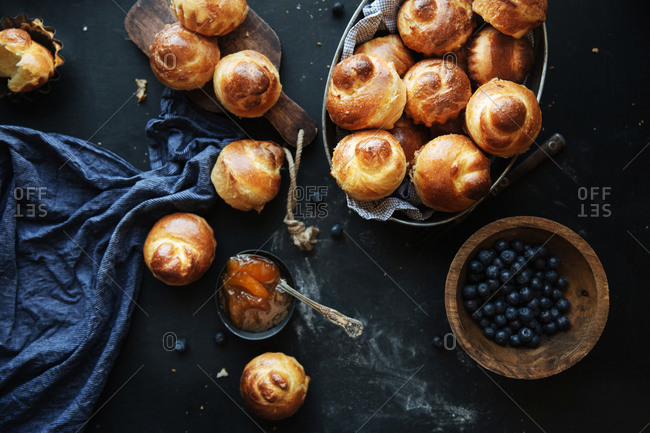 Fresh brioche rolls and blueberries in a wooden bowl