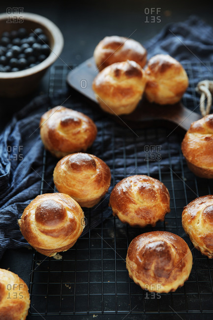 Flaky brioche rolls on a wire rack with blueberries