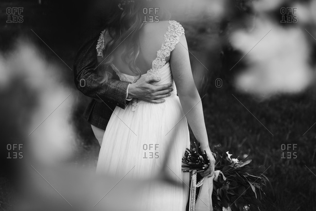 Groom standing with arm around bride