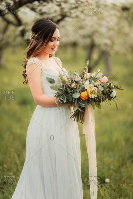 Bride standing in an orchard holding a bouquet
