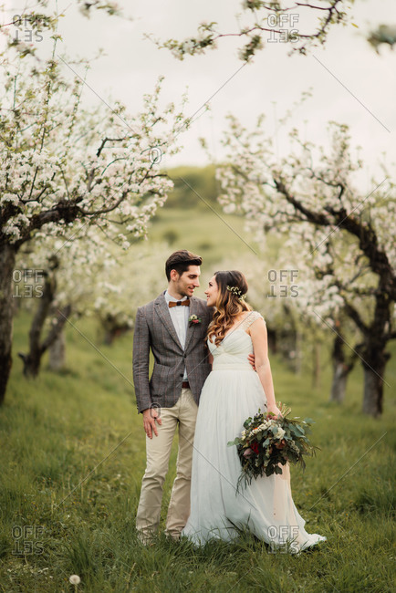 Newlyweds standing in an orchard