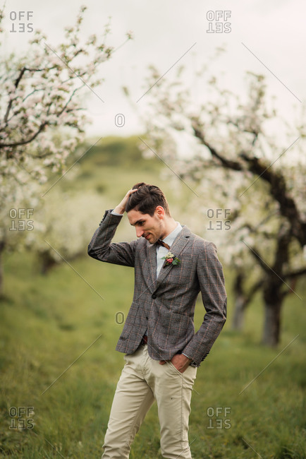 Groom running hand through his hair in an orchard