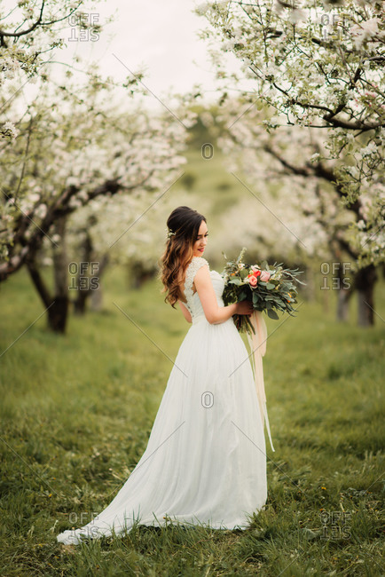Bride standing in an orchard with a bouquet