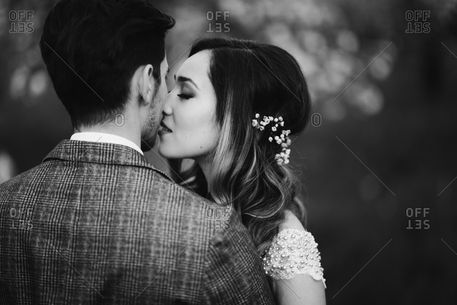 Bride and groom kissing in an orchard in black and white