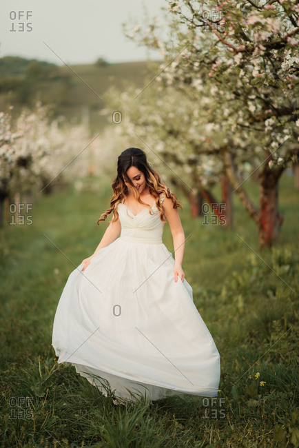 Bride twirling in an orchard