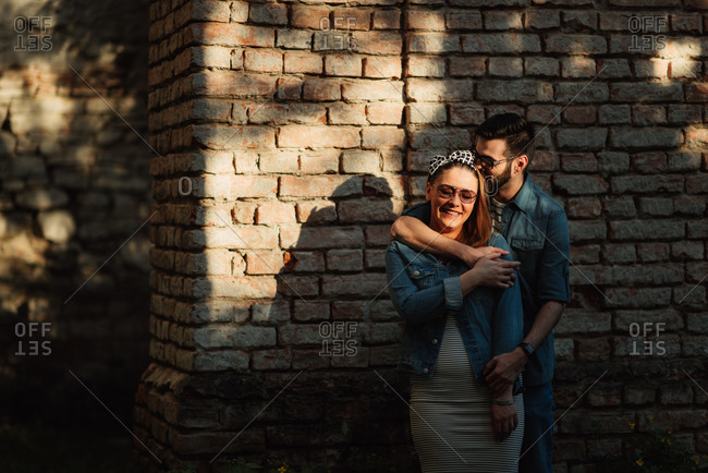 Couple standing by a brick wall