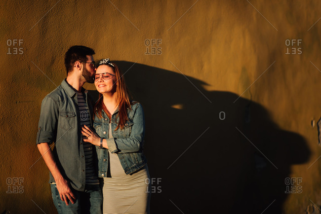 Man kissing woman while leaning on a wall together