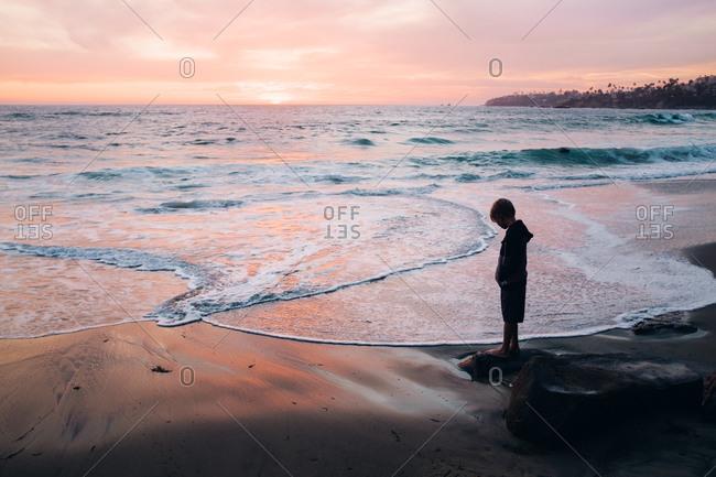 Boy looking at beach at dusk