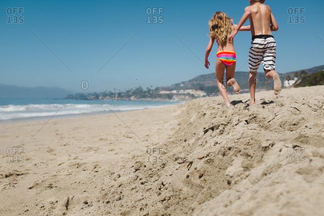 Girl and boy running on beach