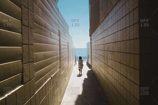 Girl walking between coastal buildings