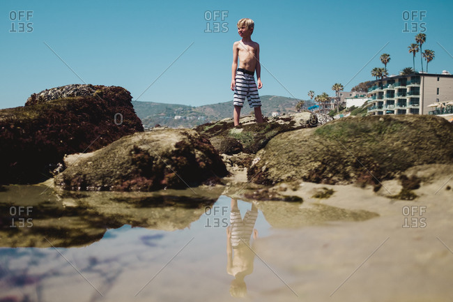 Boy reflected in water on beach
