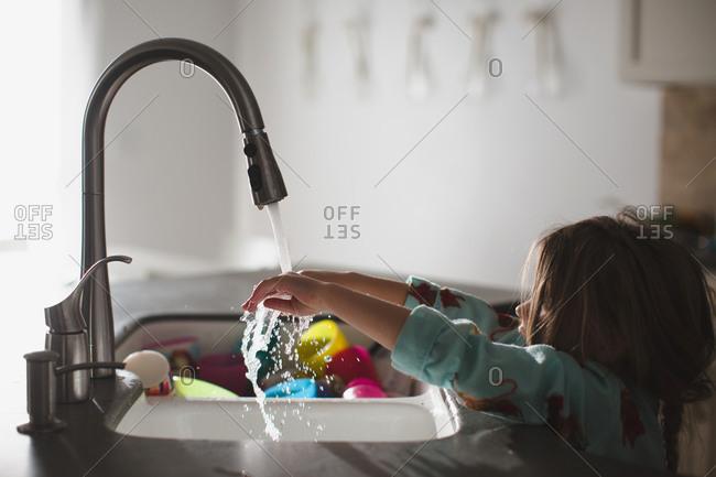 Girl rinsing hands at kitchen sink
