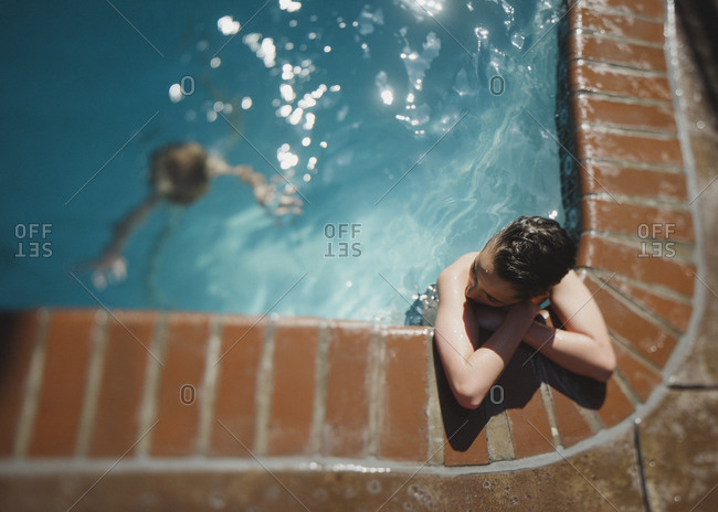 Boy resting at pool's edge