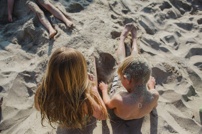 Kids covering themselves in sand