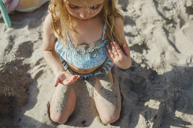 Girl covering herself in sand
