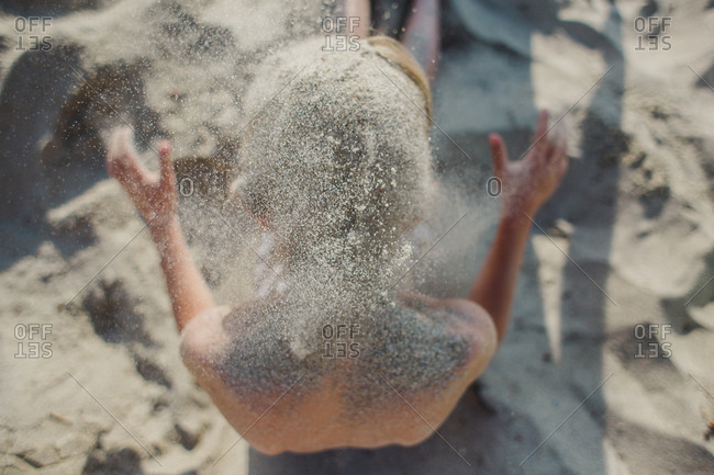 Boy covering himself in sand