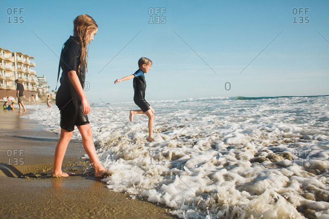 Kids in wetsuits on beach