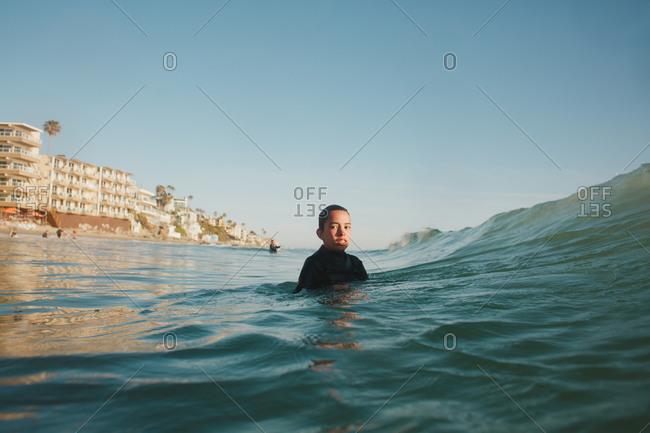 Boy standing in ocean water