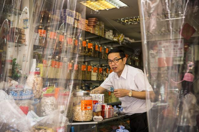 Hong Kong, China - September 16, 2015: Shopkeeper working in traditional herbal medicine store in Hong Kong