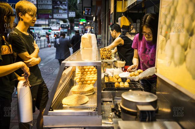 Hong Kong, China - September 16, 2015: Young people buying a snack at a street food stand, Hong Kong