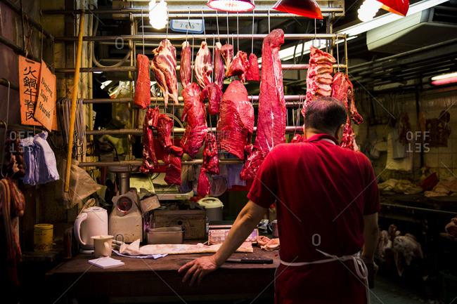 Butcher at his shop in Bowrington Road Market, Hong Kong