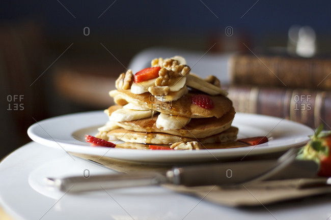 A stack of pancakes served with bananas, berries, and nuts