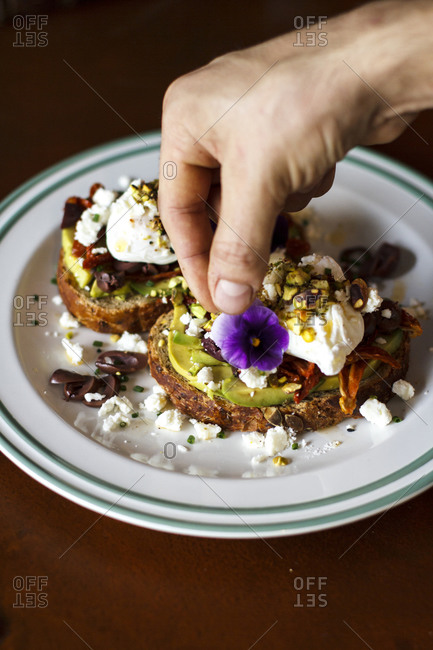 Open-faced sandwich served with cream and a flower