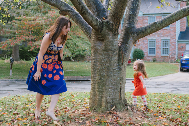 Mother chasing her daughter around a tree