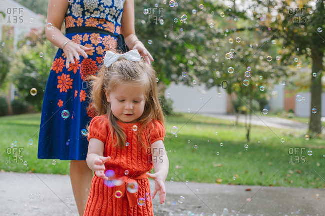 Toddler girl chasing after bubbles while her mother stands behind her