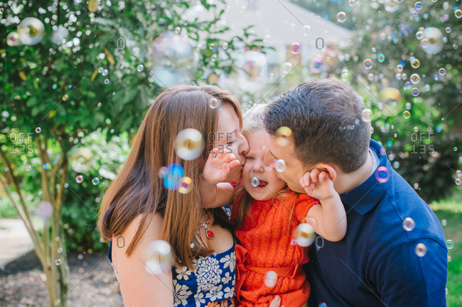 Little girl embraced by her mother and father while surrounded by bubbles
